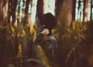 Una joven camina en un bosque llevando un sombrero negro